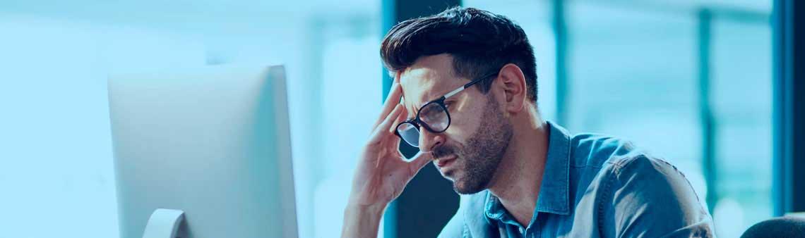 Homem frustrado na frente do computador no ambiente de trabalho