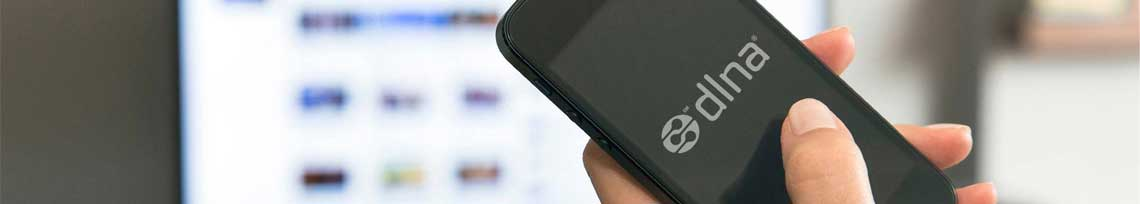 Mulher com smartphone na mão com logo do DLNA na tela e uma TV ao fundo